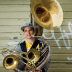 Photo of Adam Theis holding a tuba and trombones