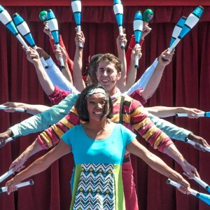 Photo of Circus Bella cast standing single file with juggling clubs spread out