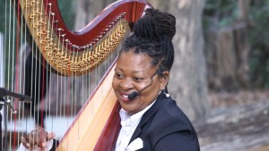 Photo of Destiny Muhammad playing the harp