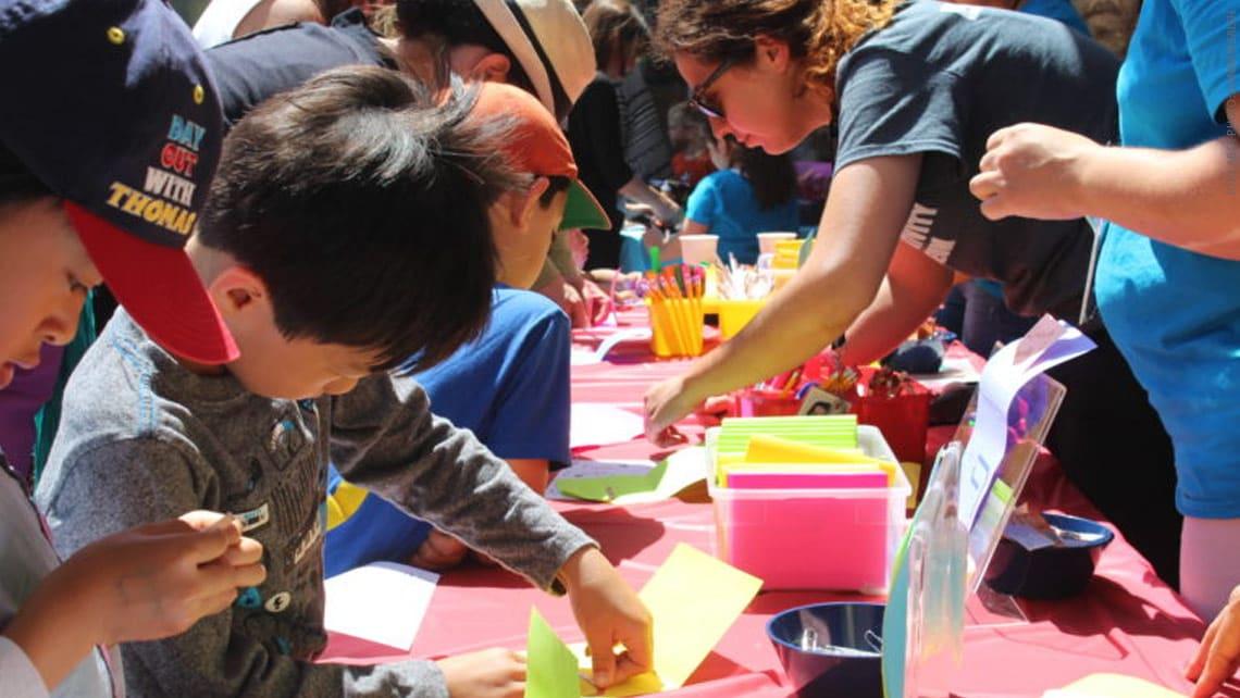 Photo of kids making paper crafts.