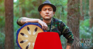 Photo of a man wearing a brimmed hat and camouflage shirt, seated outdoors, one arm resting on an octogonal drum.