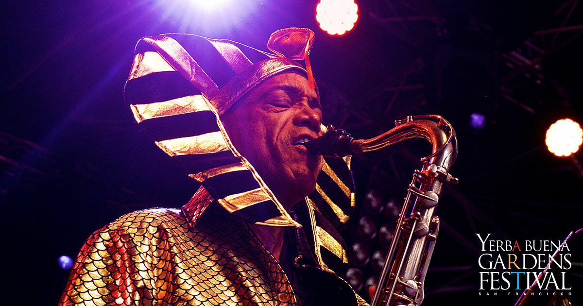 Close up of Idris Ackamoor playing a saxophone, wearing a gold top and ancient Egyptian type headdress, with colorful stage lights streaming above and behind him.