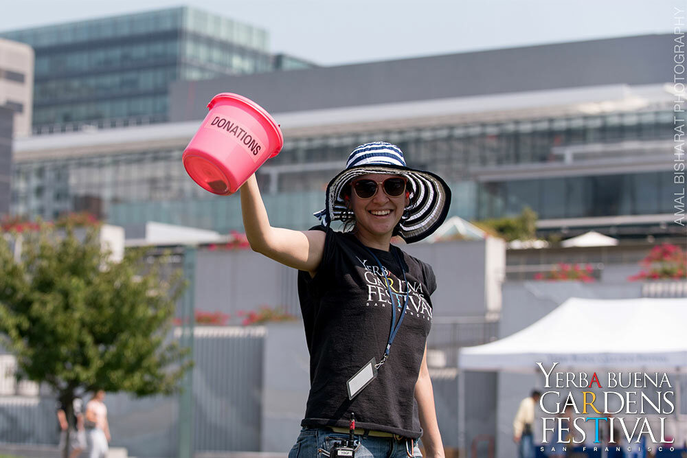 Smiling Yerba Buena Gardens Festival Event Staff member holding out a pink donations bucket.