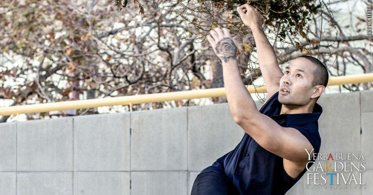 A male dancer, wearing a dark blue sleeveless top, leaning down toward the right, with arms up from the left, as if he is in free fall. outside in front of a concrete wall.