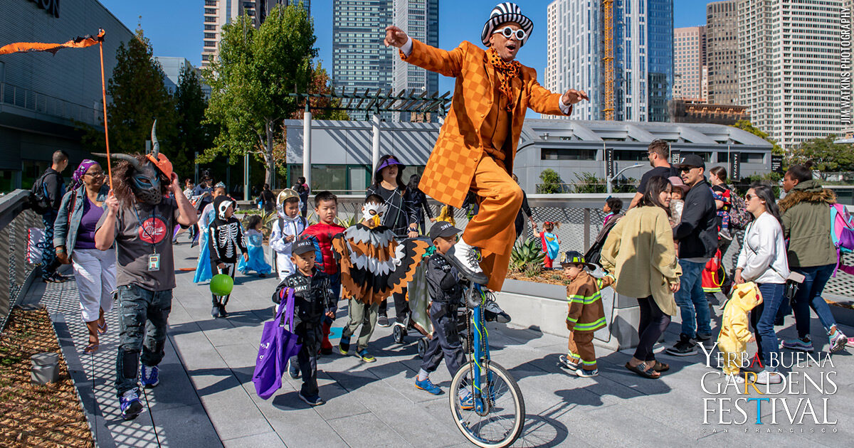 Unique Derique riding a high tricycle, leading the annual Halloween Hoopla Costume parade with dozens of costumed kids and their adults behind him.