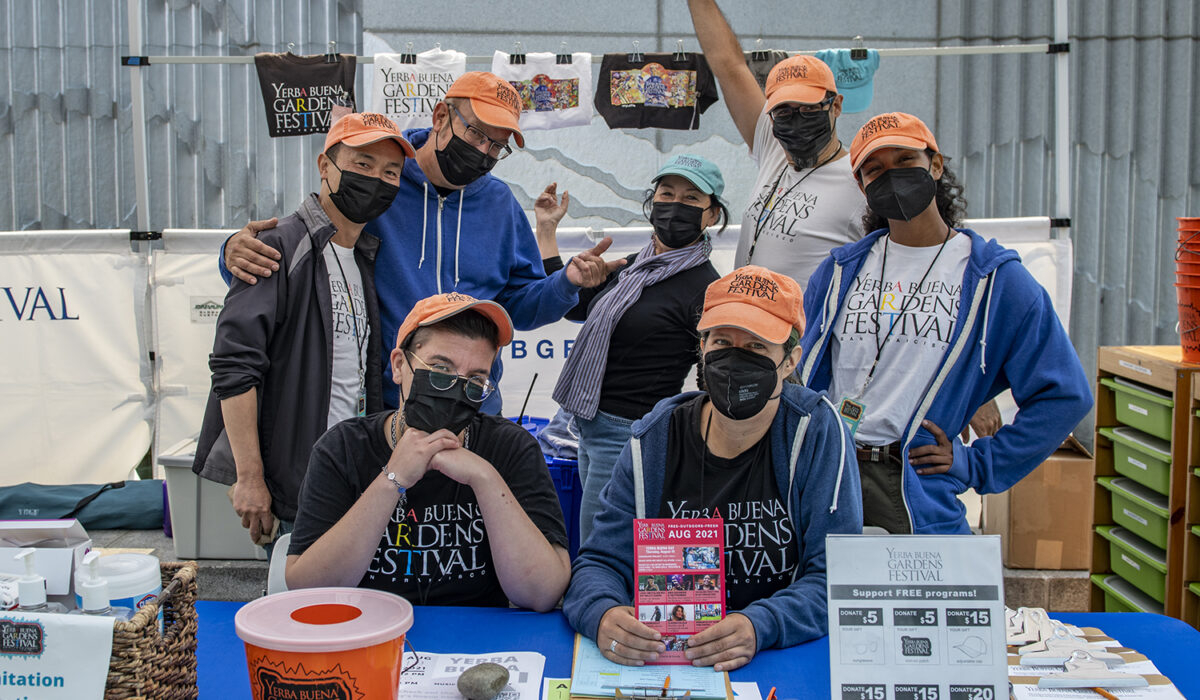 YBG Festival staff wearing masks and Festival hats, posing for the photo at the YBG Festival Info table